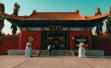 person walks towards temple