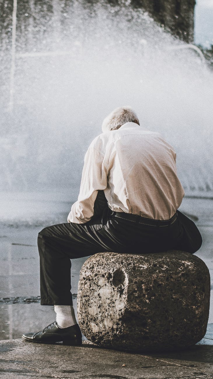 man sitting on rock in front of water fountain